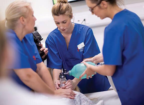 Student nurses simulating giving a patient oxygen