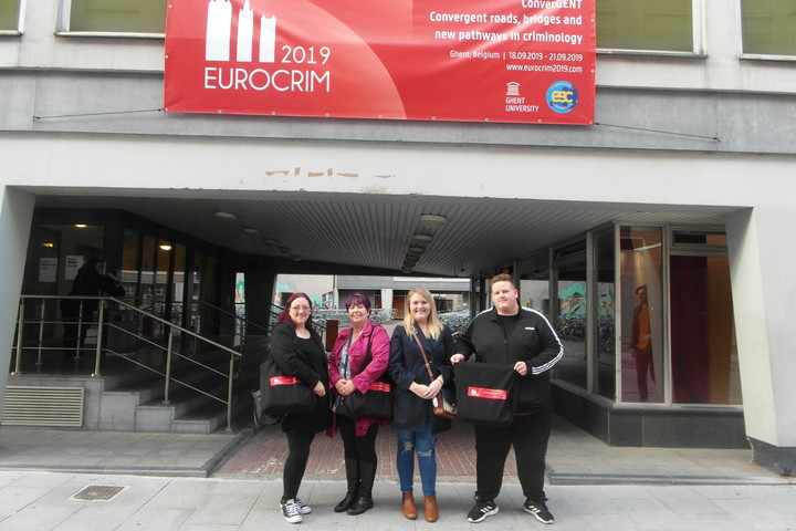 Four Criminology students standing smiling to camera, under a banner about a Criminology conference