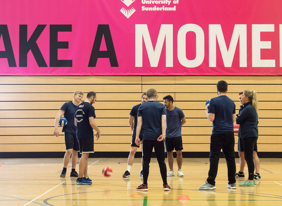 A group of student taking part in a practical session in the sports hall in CitySpace